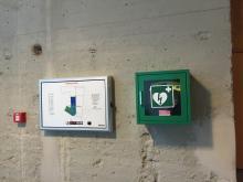 De AED / hartdefibrillator hangt naast de achteringang in de centrale hal